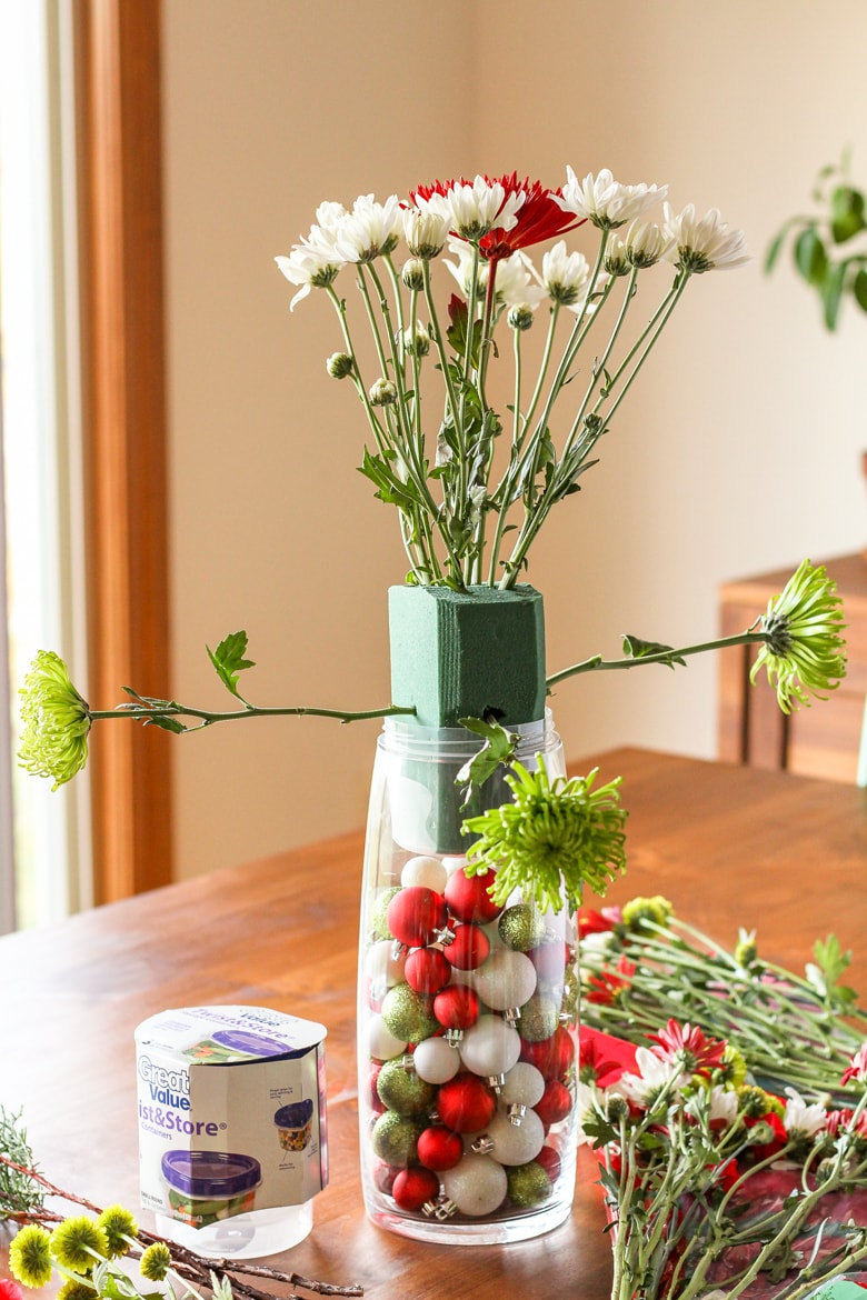 christmas flowers arrangement in wet floral foam with christmas ornaments