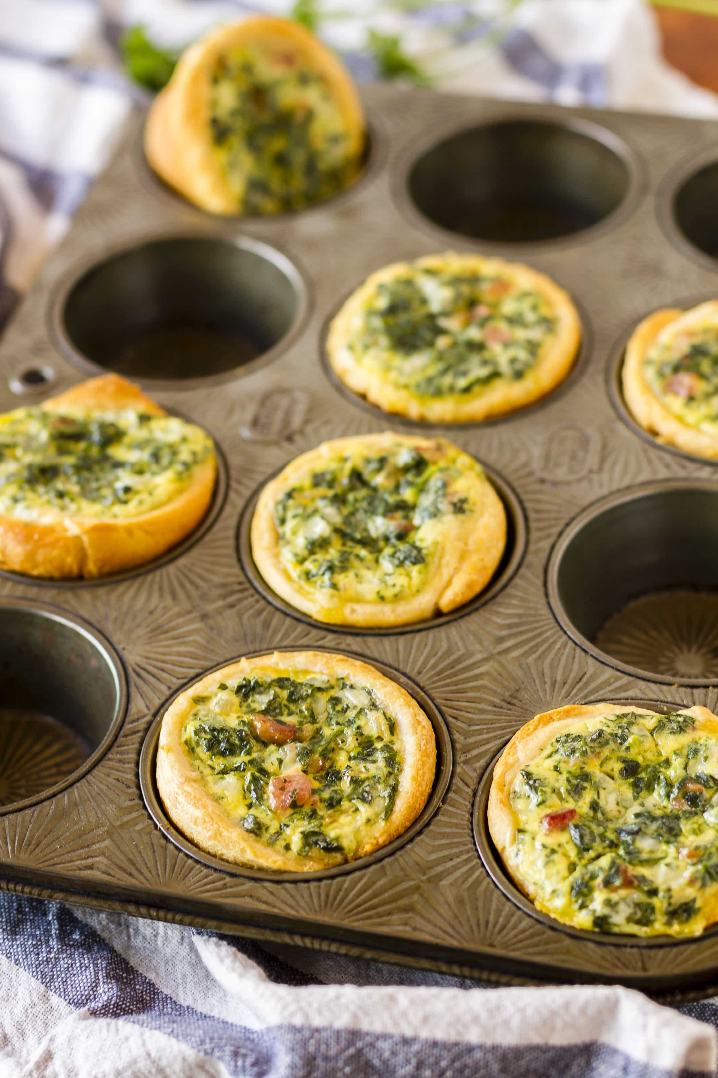 Mini Spinach Quiche -- these cute little mini quiche filled with spinach and bacon are a delicious and filling brunch idea! They're also very tasty cold, making them an excellent on the go breakfast option…   easy mini spinach quiche   mini spinach quiche recipe   mini spinach quiche brunch   mini spinach quiche crescent rolls   find the recipe on unsophisticook.com