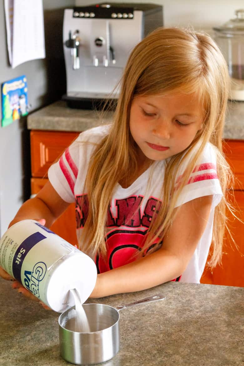 young girl adding salt to an easy recipe for salt dough