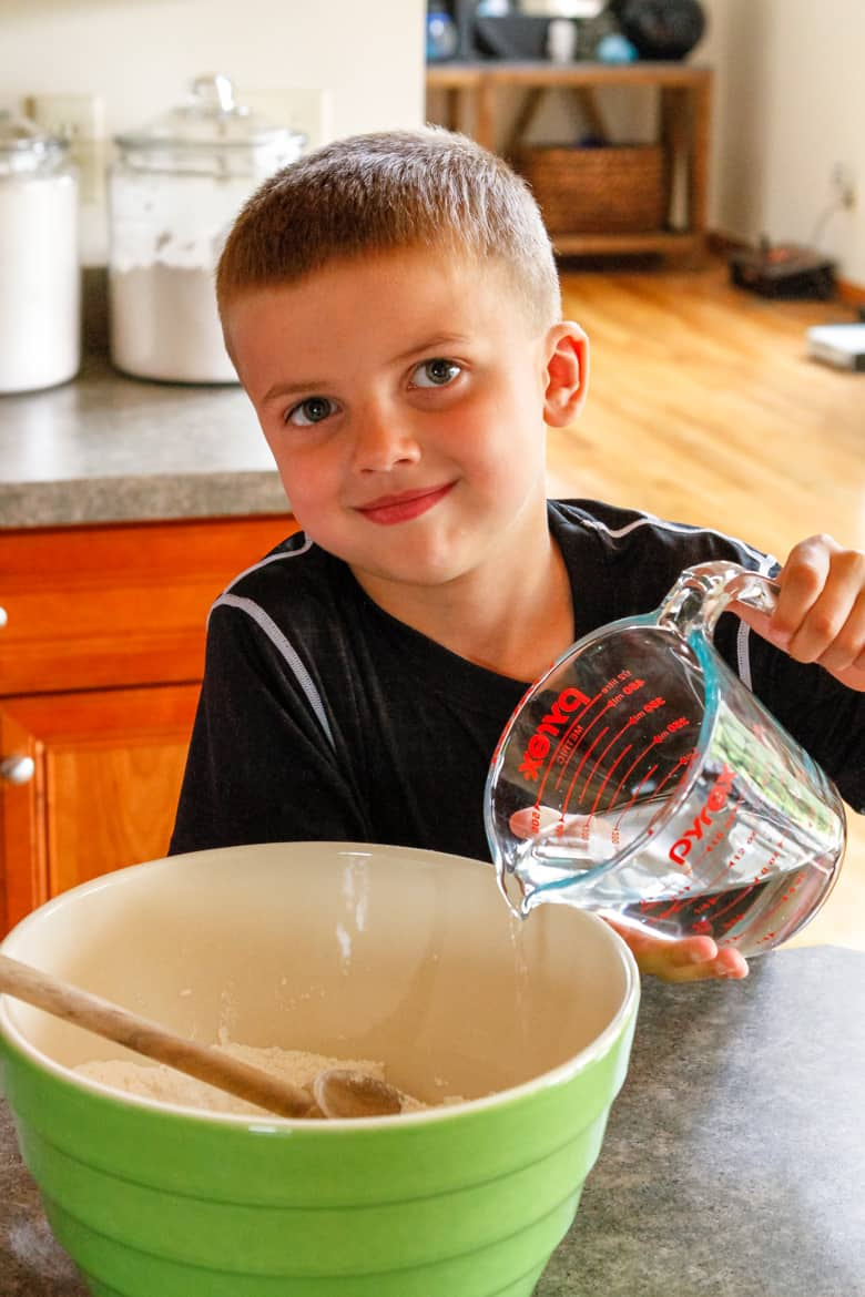 young boy adding water to salt dough for salt dough crafts