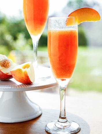 Frozen Peach Bellini Recipe -- this beautiful peach bellini recipe is the perfect fresh and fruity cocktail for sipping on a warm summer evening!