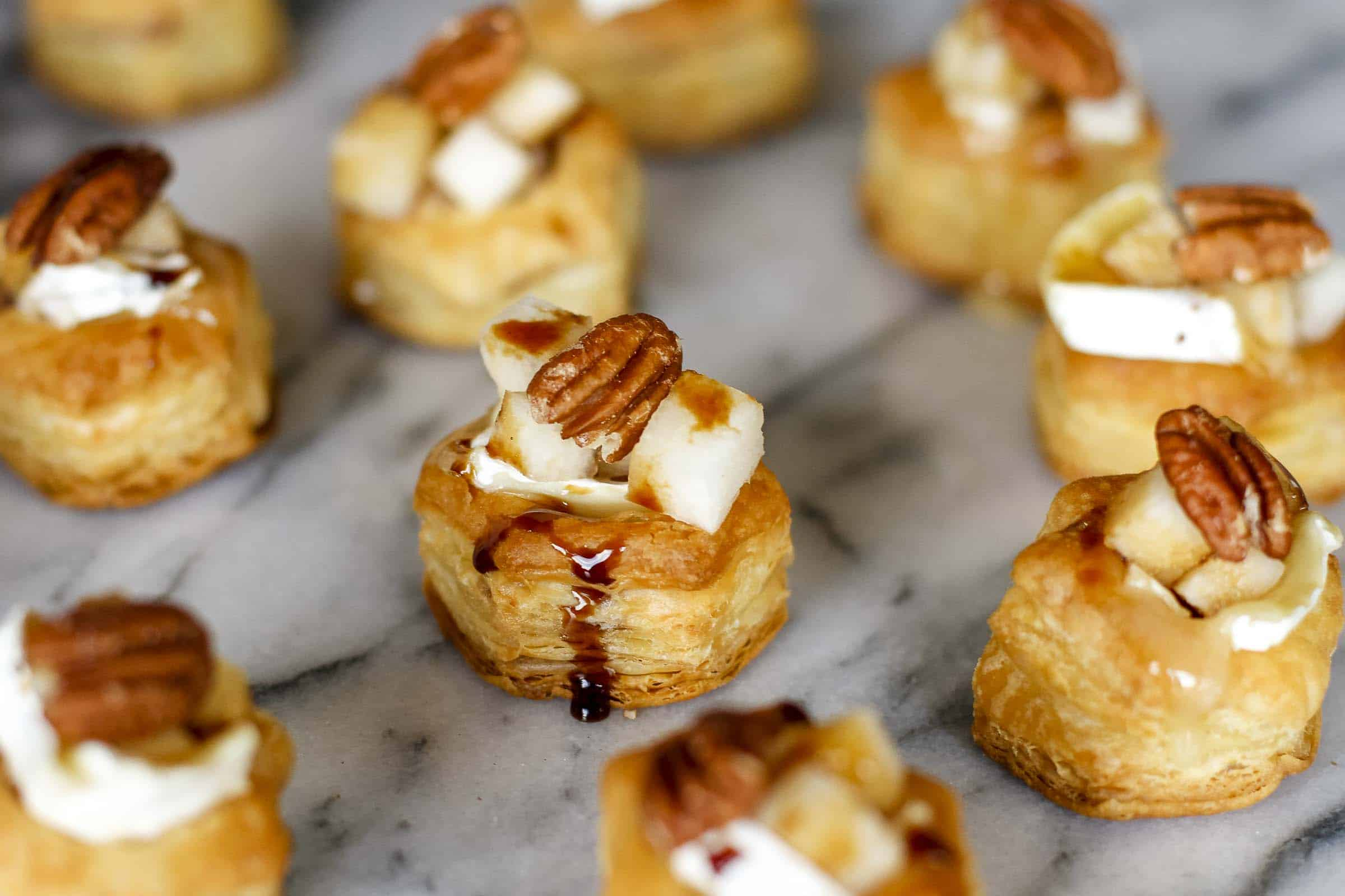 Baked Brie Bites -- these delicious baked brie bites are topped with diced pears, toasted walnuts and a drizzle of balsamic reduction for a fabulous holiday appetizer! | via @unsophisticook on unsophisticook.com