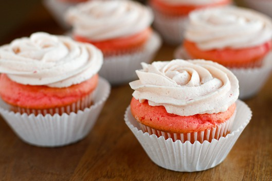 fresh strawberry buttercream frosting piped on pink velvet cupcakes