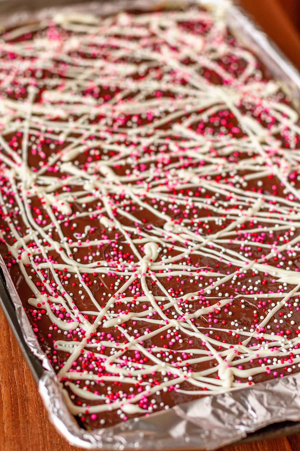 saltine cracker crack recipe on a baking sheet with sprinkles on top