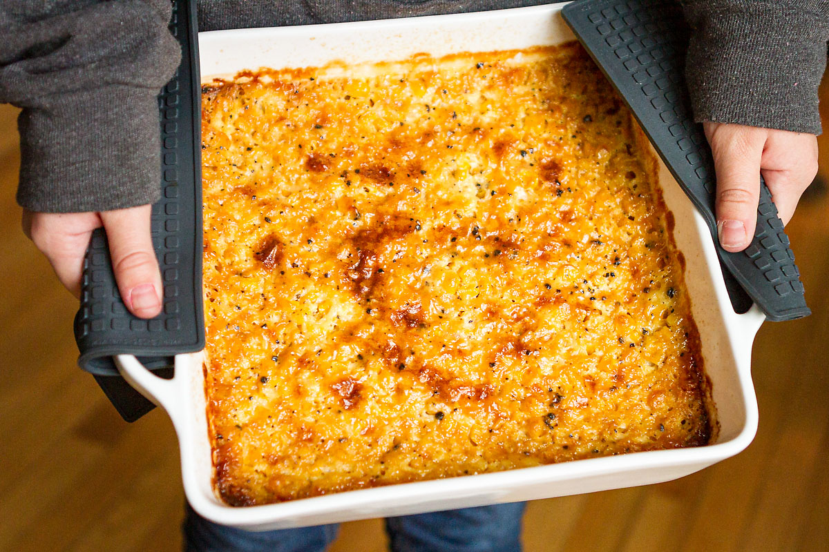 favorite of all corn casserole recipes in a white casserole dish with gray silicone pot holders