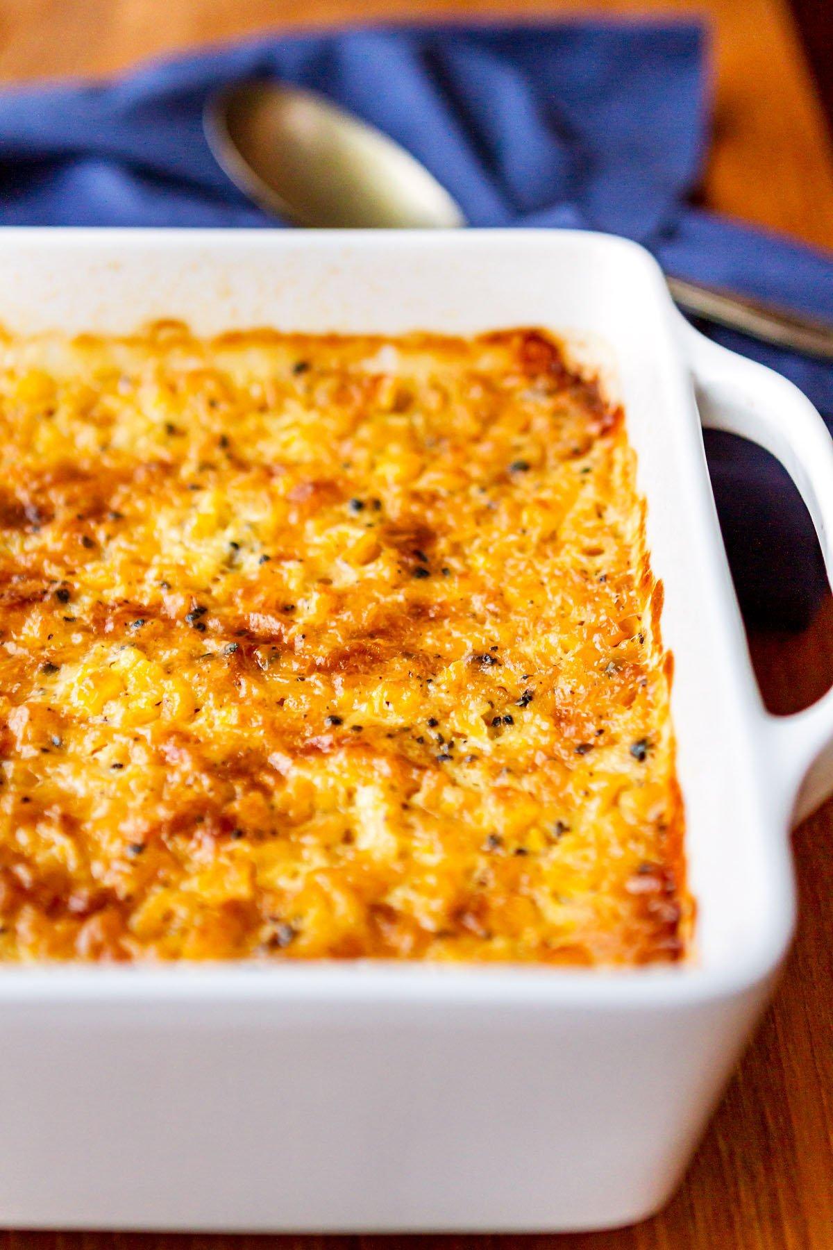 corn casserole like grandma made it in a white casserole dish with royal blue napkin