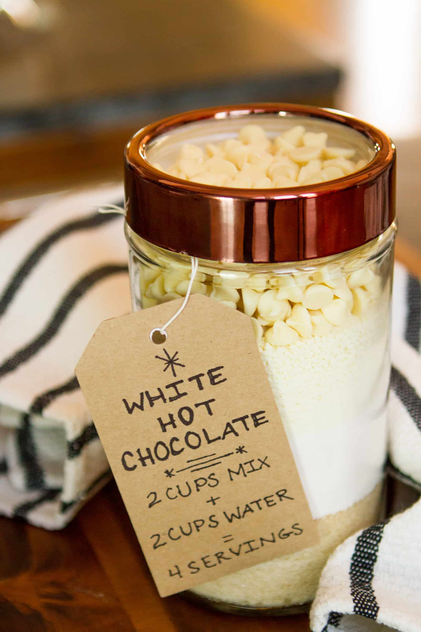 White Hot Chocolate Mix -- a new twist on the classic mason jar gift idea, this tasty white hot chocolate mix is layered in a gorgeous glass storage jar with copper-colored lid from At Home… Perfect as a teacher gift, thank you gift, hostess gift, etc! | via @unsophisticook on unsophisticook.com
