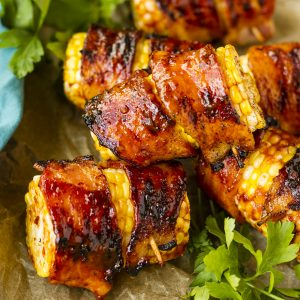 Sweet & Spicy Bacon Wrapped Corn On The Cob -- does it get any better than bacon + corn + a sweet & spicy honey chipotle glaze? THIS is the recipe that all your guests will be asking for after your next cookout! | grilling recipes | summer grilling recipes | corn on the cob on the grill | grilled bacon wrapped corn | corn on the cob recipes | find the recipe on unsophisticook.com