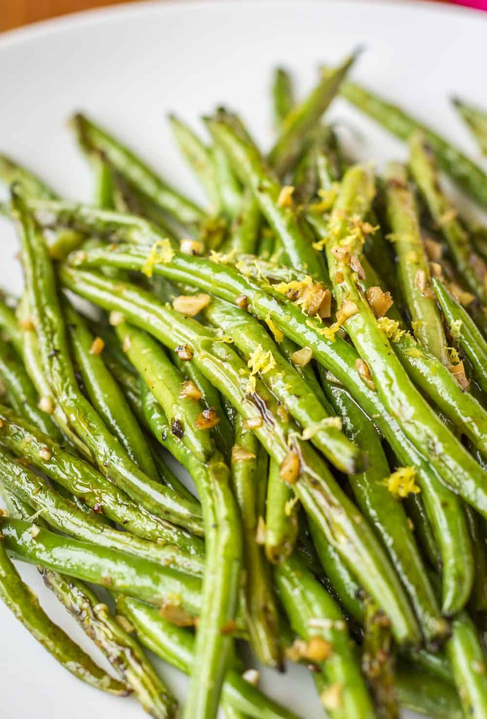 Sautéed Green Beans with Garlic -- adding a little extra raw minced garlic to these sautéed green beans at the end of cooking gives them an extra unexpected punch of flavor… Just 4 ingredients and under 10 minutes from stovetop to table makes this a super easy side dish! | fresh green beans | green beans recipe | healthy green beans | easy green beans | how to cook green beans | find the recipe on unsophisticook.com