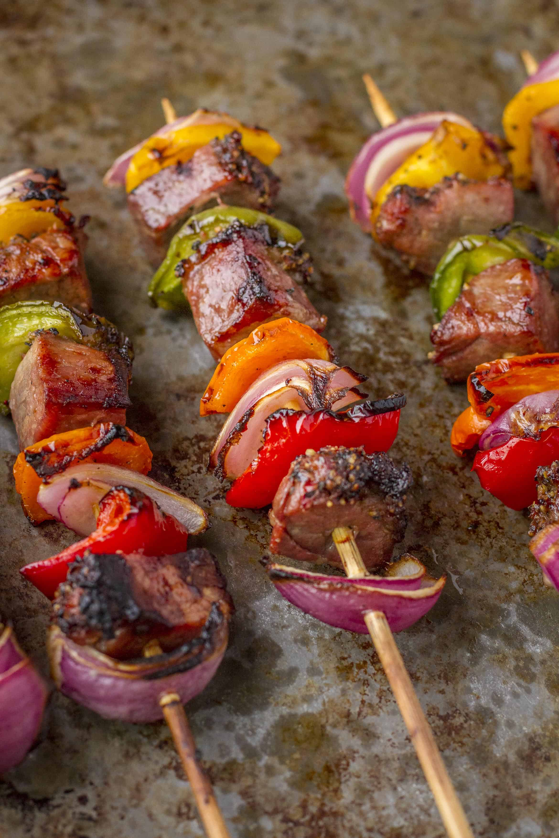 Tri-Tip Beef Kabobs -- Try these delicious tri-tip beef kabobs at your next cookout... Chunks of marinated tri-tip, with colorful red onions and bell peppers, will have your guests lining up for more! | kabobs on the grill | steak kabobs | kabobs recipe | kebabs recipe | get the recipe on unsophisticook.com