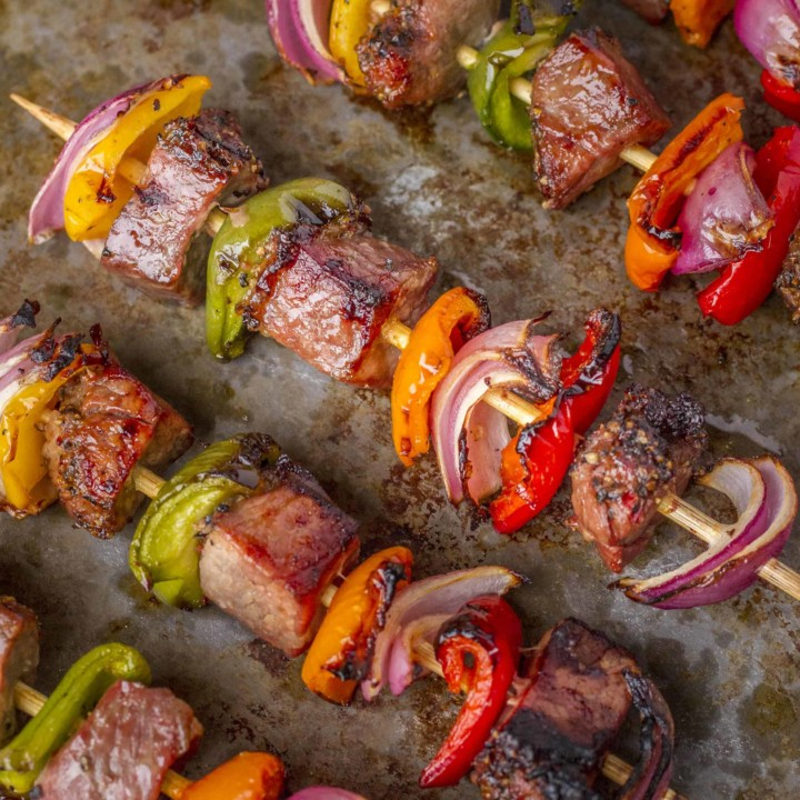 Tri-Tip Beef Kabobs -- try these delicious tri-tip beef kabobs at your next cookout… Chunks of marinated tri-tip steak, with colorful red onions and bell peppers, will have your guests lining up for more! | kabobs on the grill | steak kabobs | kabobs recipe | kebabs recipe | get the recipe on unsophisticook.com
