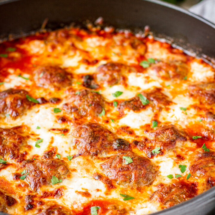 cheesy meatball casserole in a gray enamel cast iron skillet