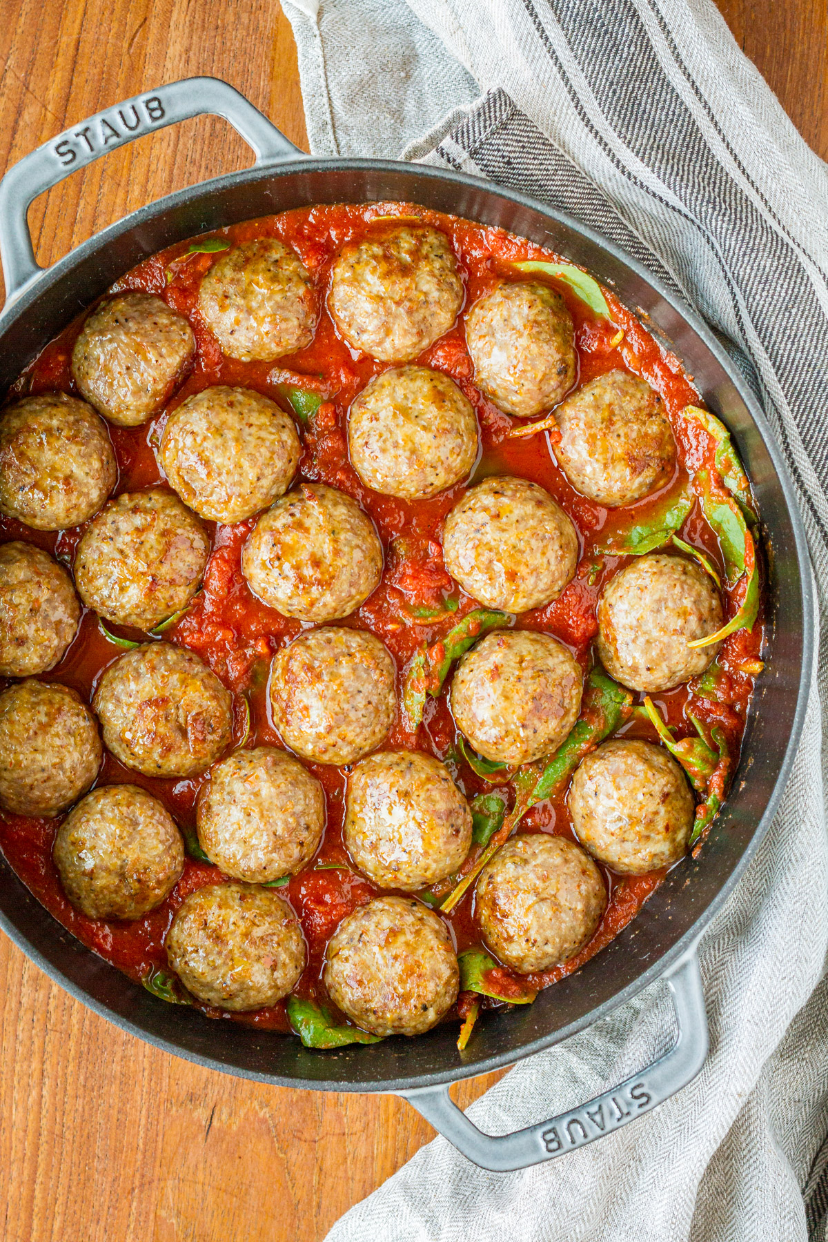 cheesy meatball recipe in a gray enamel cast iron skillet with a linen towel