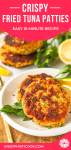 crispy fried tuna patties on a white plate garnished with lemon wedges and fresh parsley