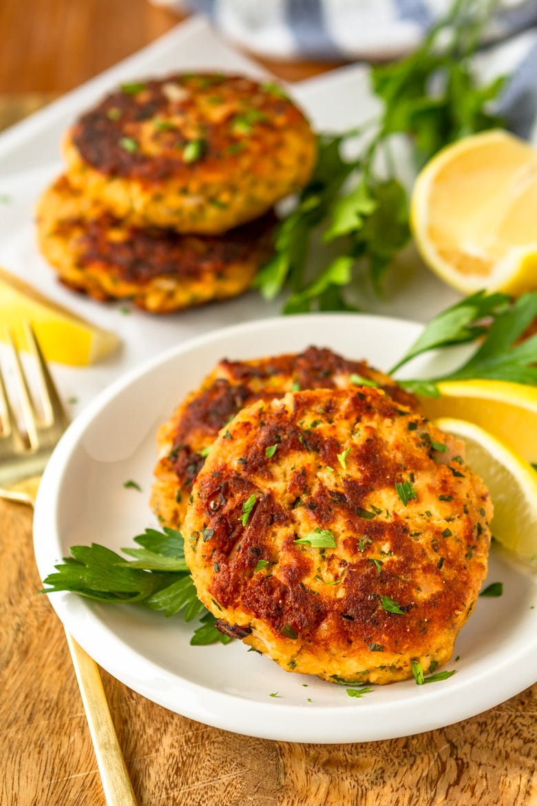 tuna cakes on a white plate with fresh parsley and lemon wedges