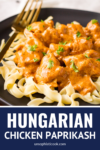 hungarian chicken paprikash recipe over egg noodles with a gold fork