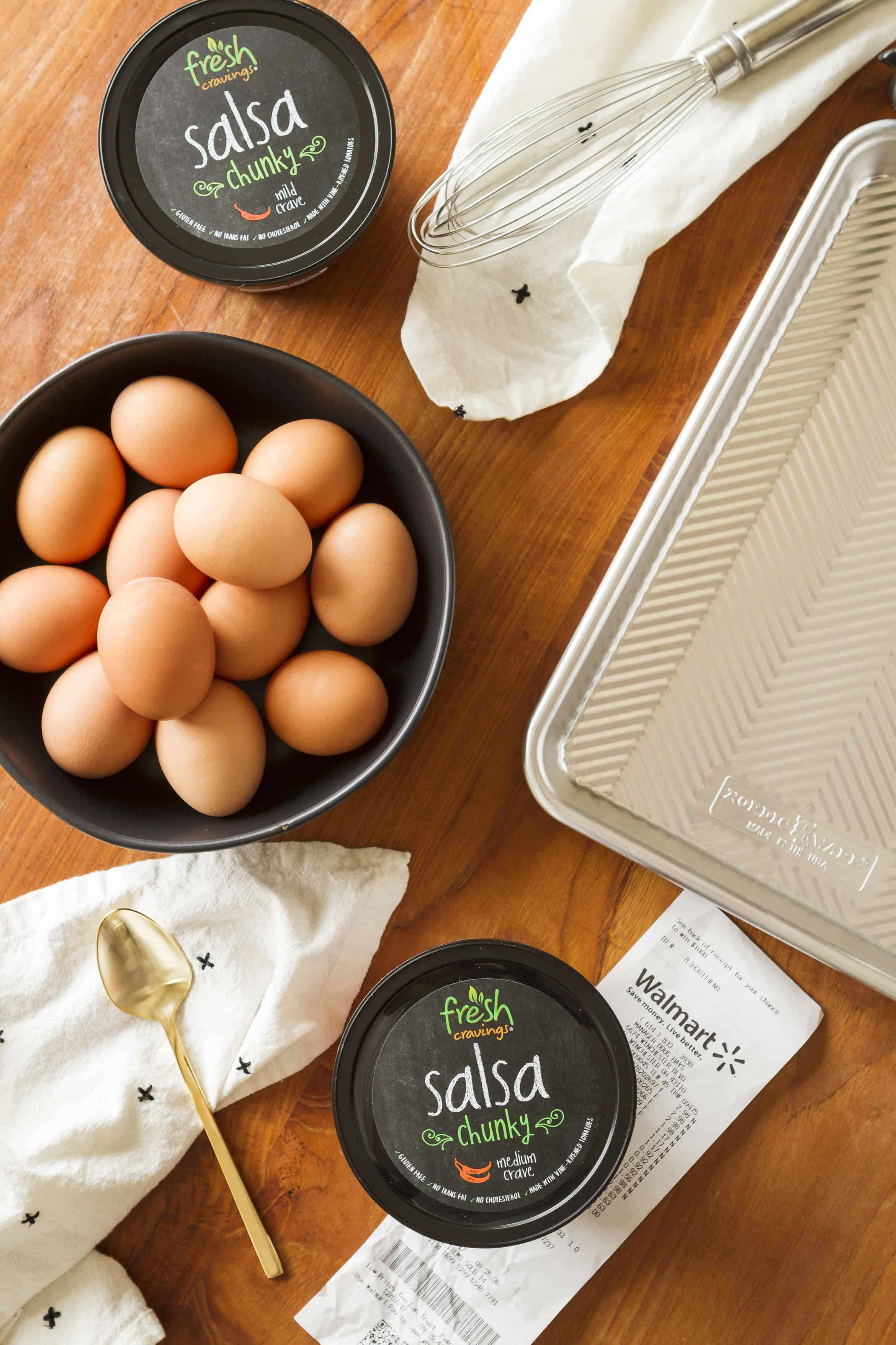 sheet pan eggs ingredients with a walmart receipt and fresh cravings salsa