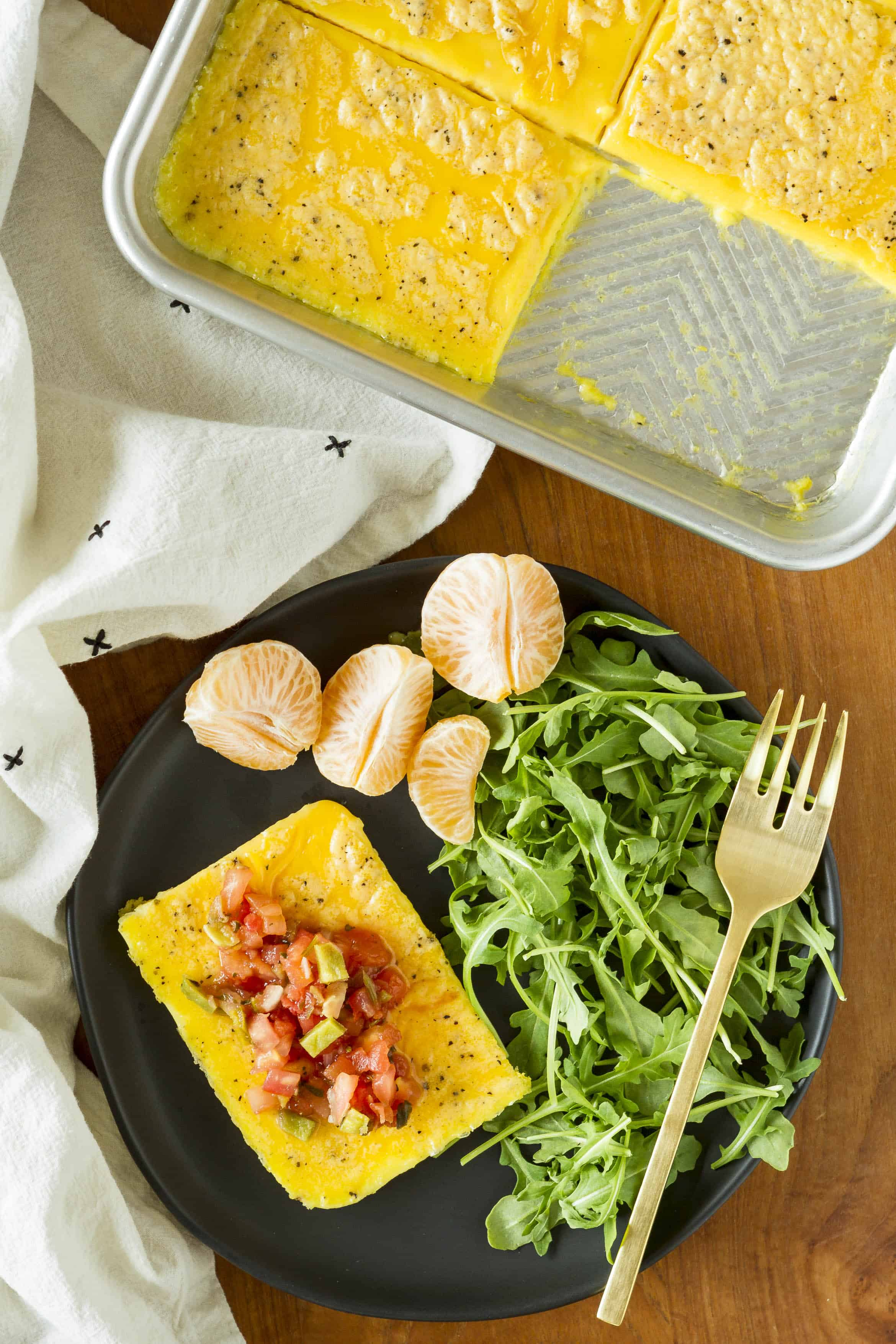 scrambled eggs cooked on a sheet pan and served on a black plate topped with salsa and a side of fresh arugula and mandarin oranges