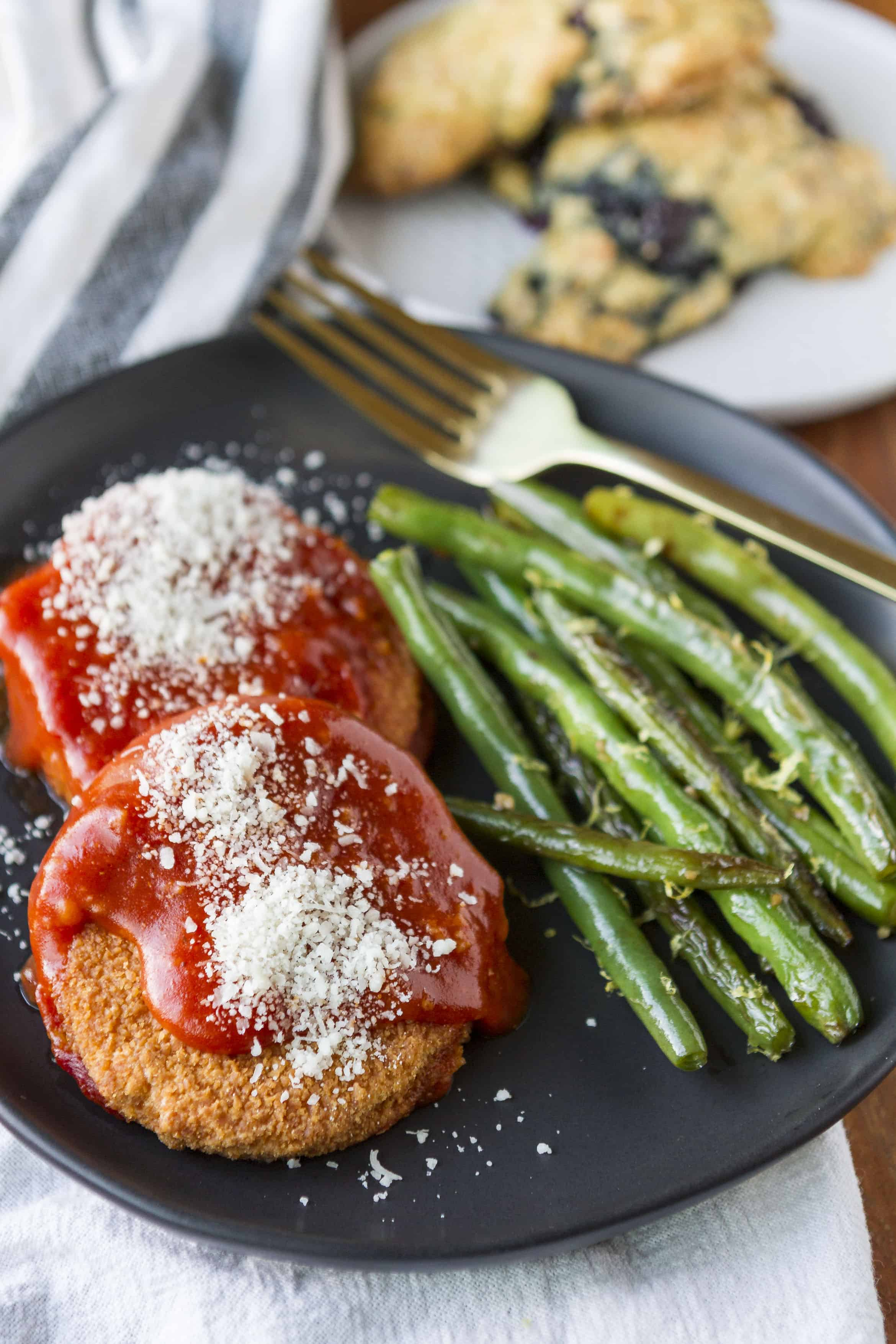 On-Cor chicken parmigiana on a black matte plate with green beans and blackberry scones