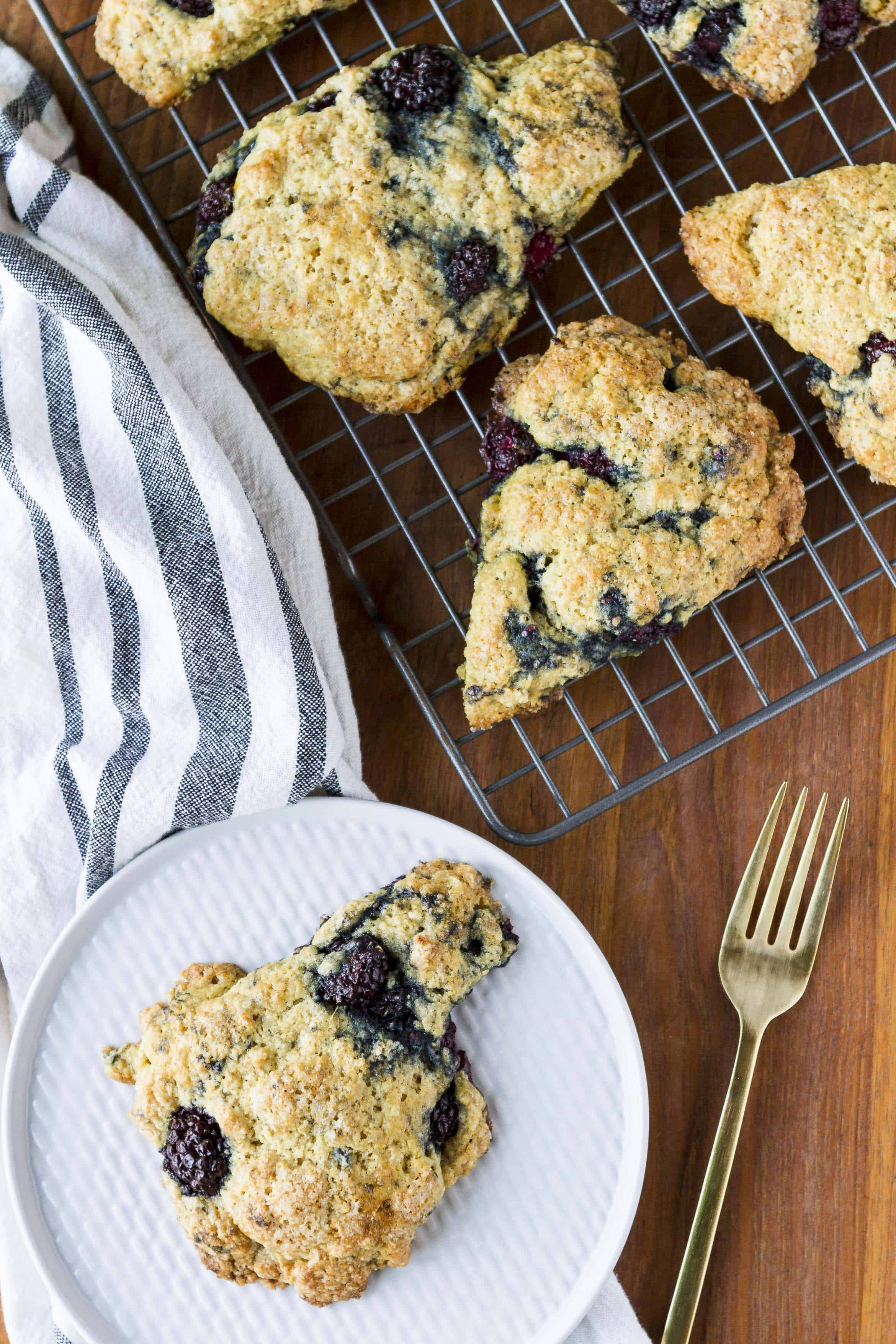 tender and buttery blackberry scones on a cooling rack with a single scone on a textured white plate with a gold fork next to it