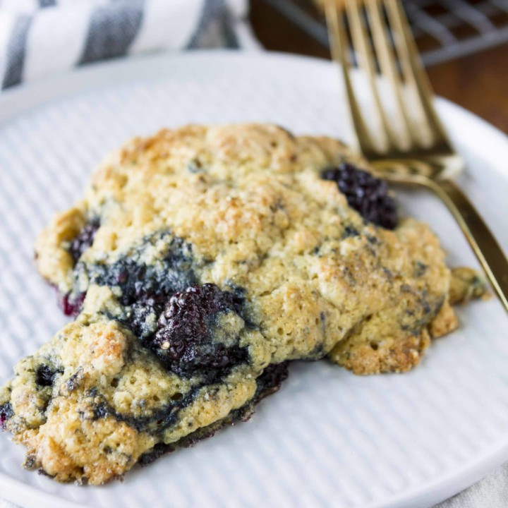 tender and buttery blackberry scone on a white textured plate with a gold fork