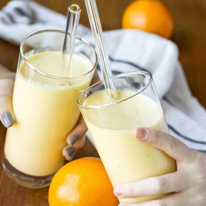 clinking glasses filled with orange mango healthy citrus smoothie