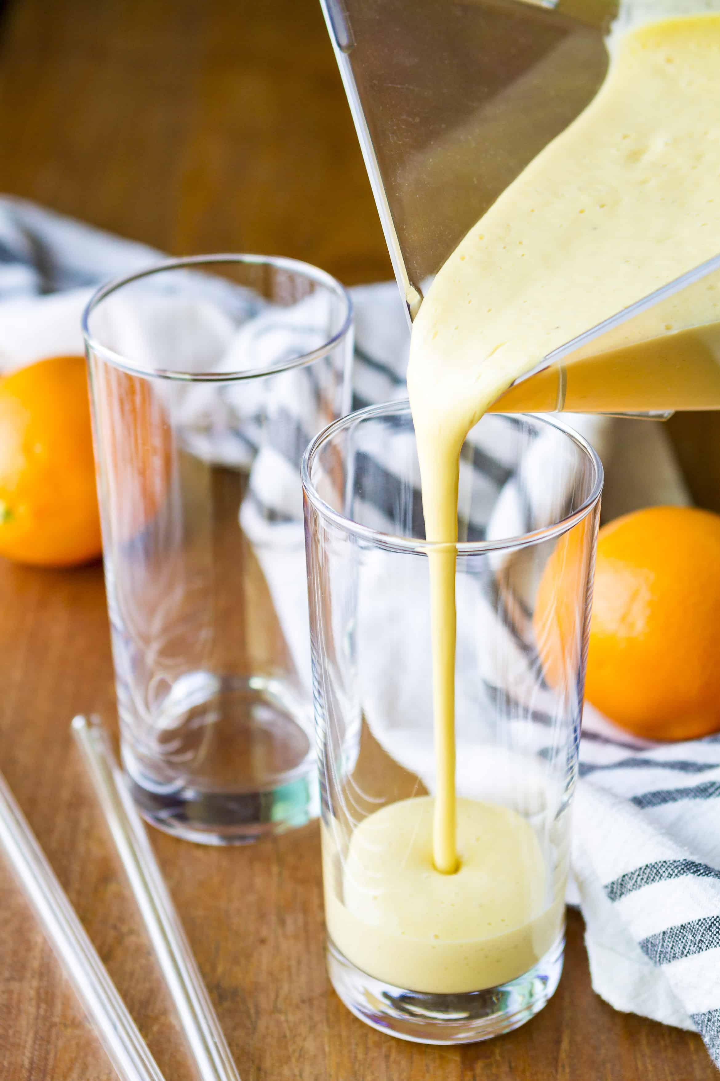 pouring orange mango healthy citrus smoothie into glasses