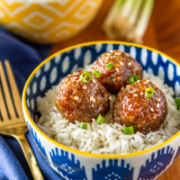 asian meatball recipe in a blue and white bowl served with coconut milk rice and topped with green onions