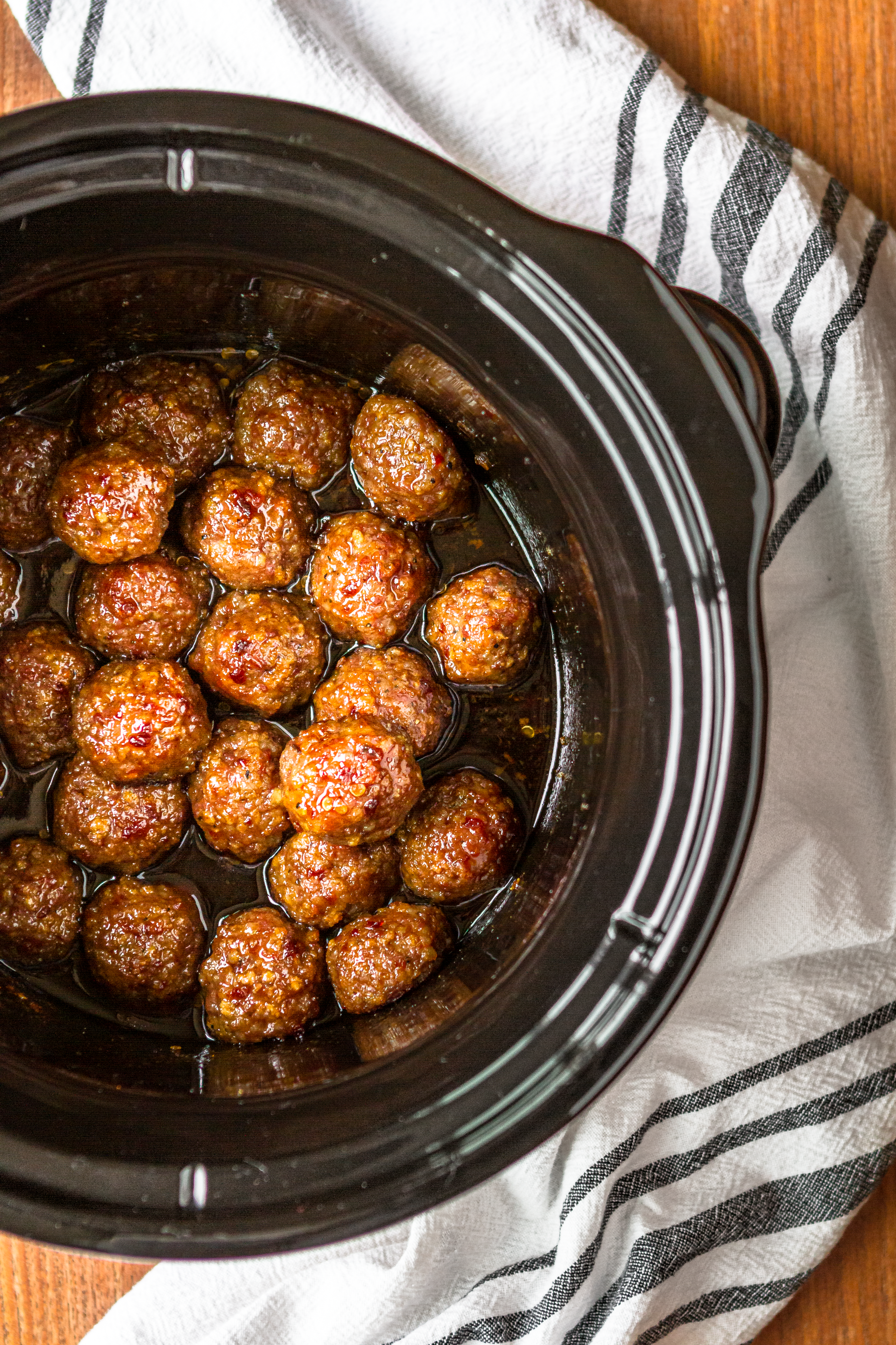 Asian meatballs crockpot view with sweet and spicy sauce and a black and white kitchen towel
