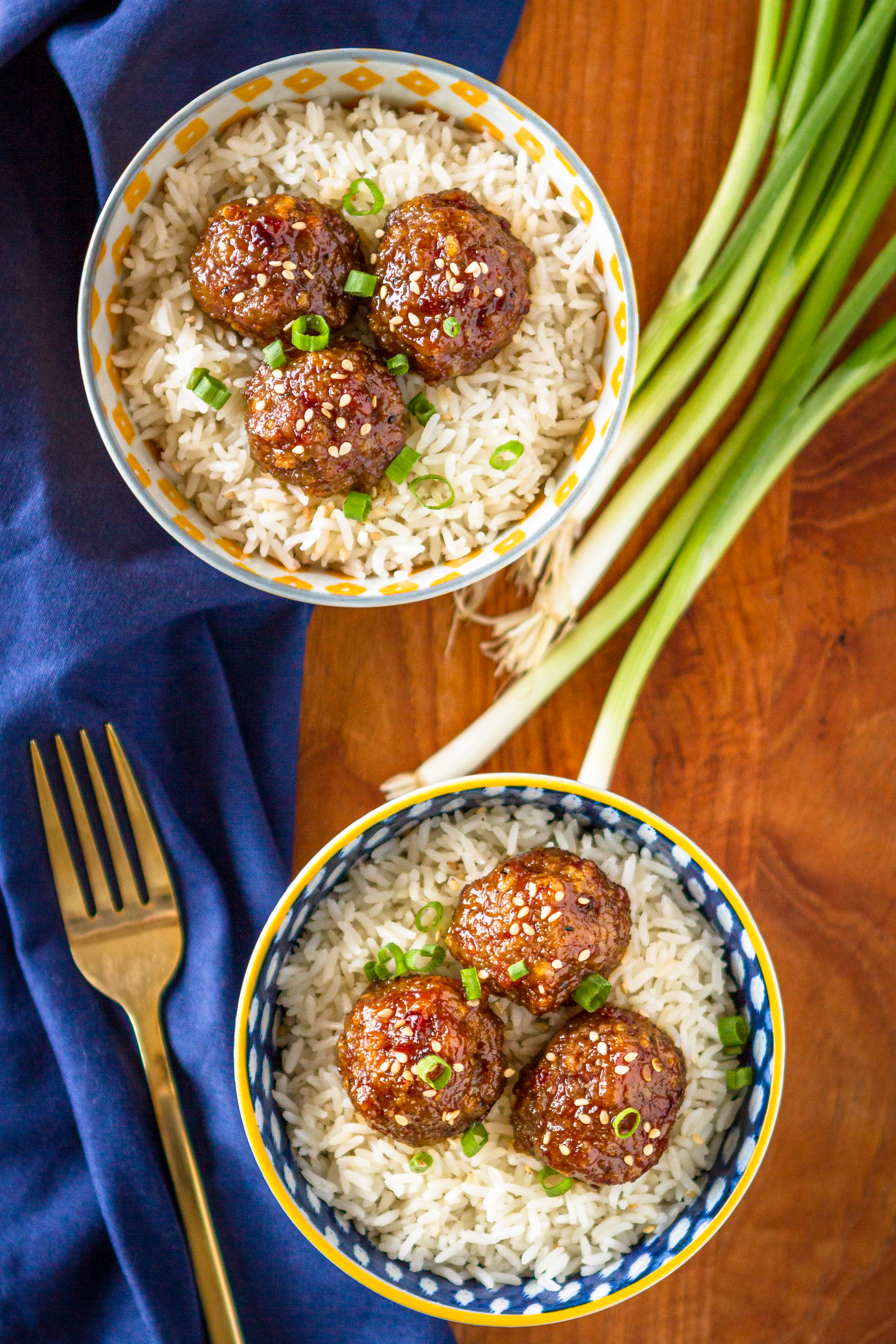 Asian pork meatballs over rice in bowls with green onions and a dark blue napkin
