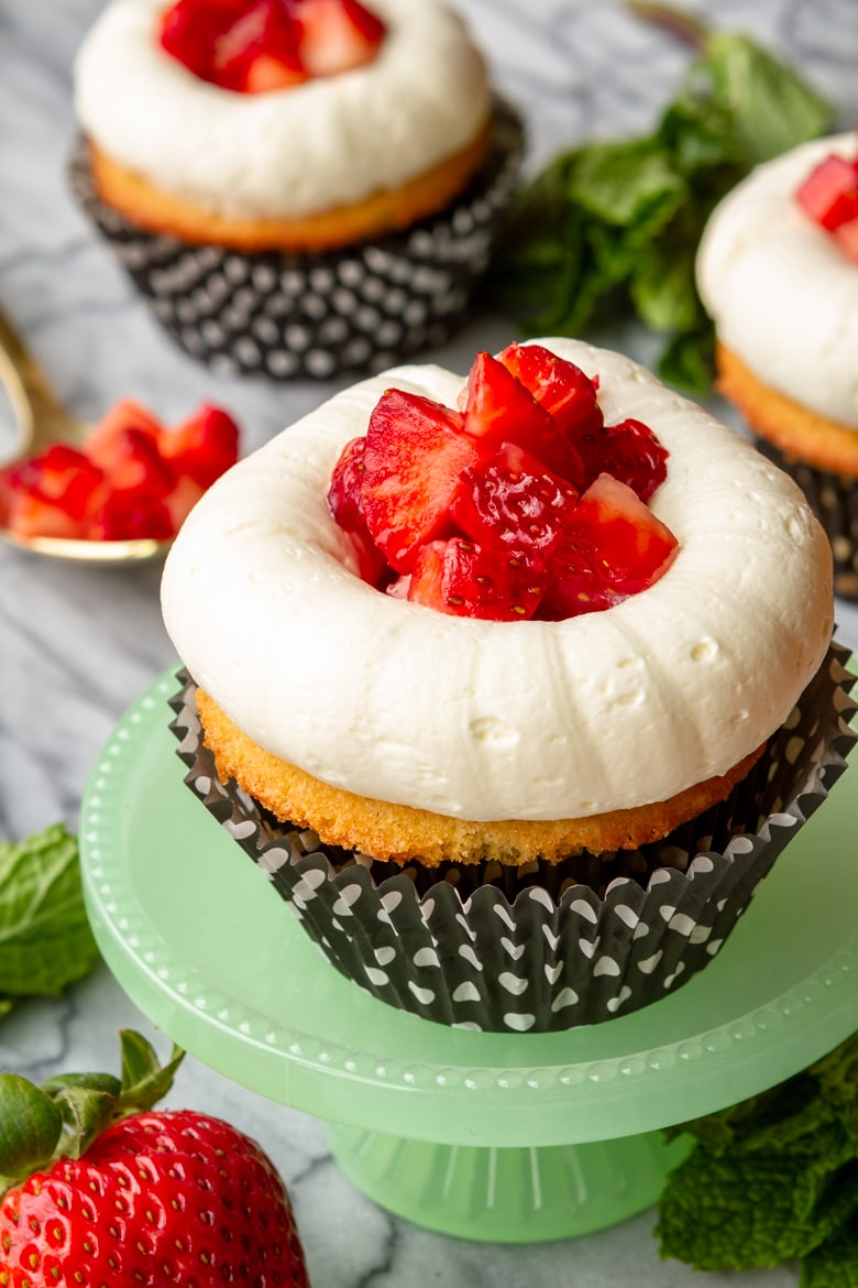 strawberry shortcake cupcakes topped with fresh strawberries and buttercream frosting