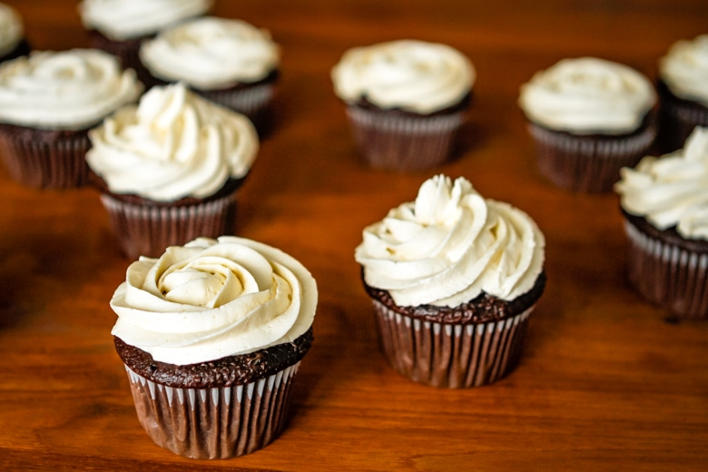 whipped buttercream frosting piped on chocolate cupcakes