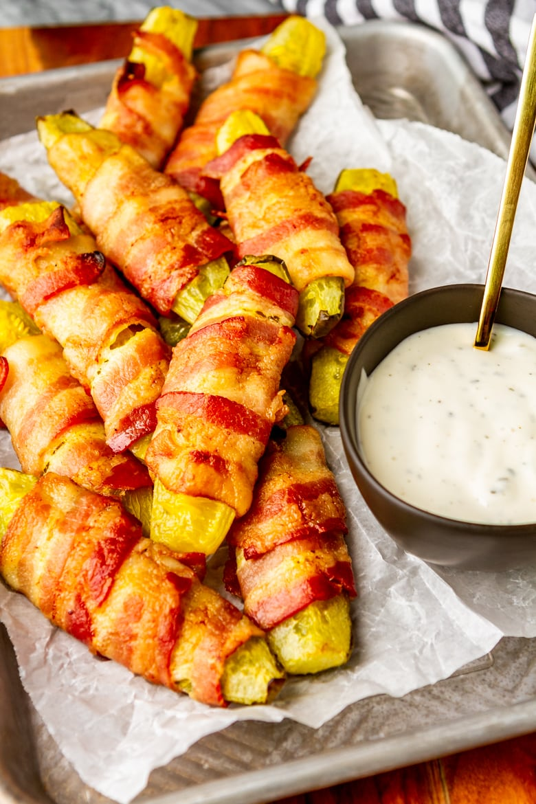 bacon wrapped pickles low carb and keto friendly served with ranch dressing