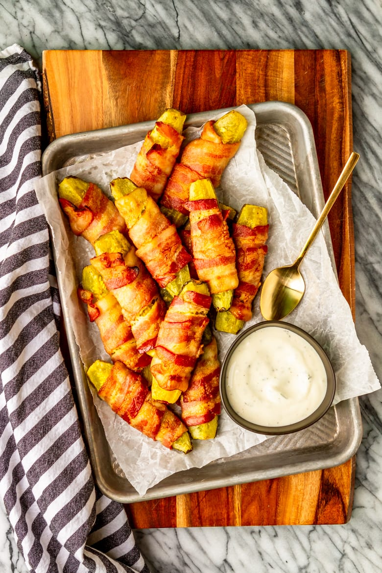 bacon wrapped pickles on a tray served with ranch dressing