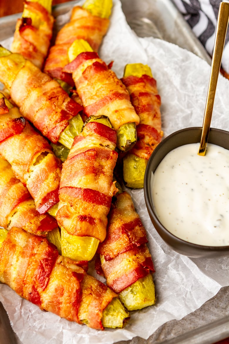pickle wrapped in bacon with a bowl of ranch dressing