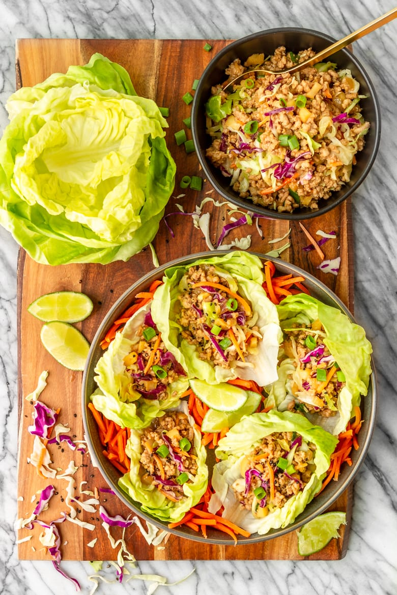 easy pork lettuce wraps recipe made with ground pork on a wooden cutting board with stacked bibb lettuce