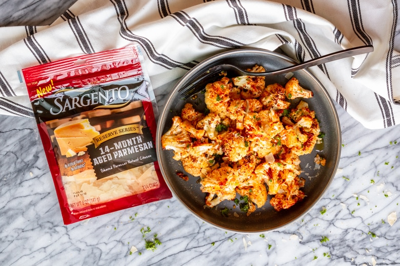 garlic parmesan roasted cauliflower in a gray bowl with Sargento Reserve Series 14-Month Aged Parmesan package