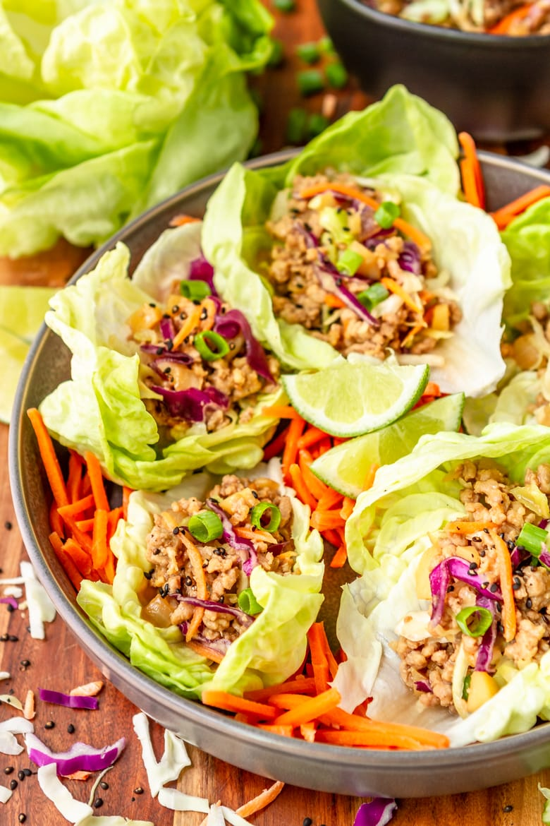 ground pork lettuce cups nestled in a gray bowl with a stack of boston bibb lettuce