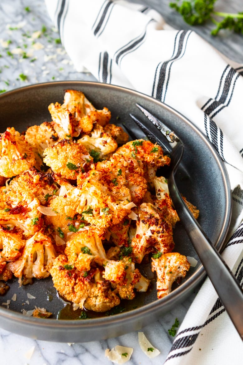 parmesan roasted cauliflower in a grey bowl with a black and white kitchen towel