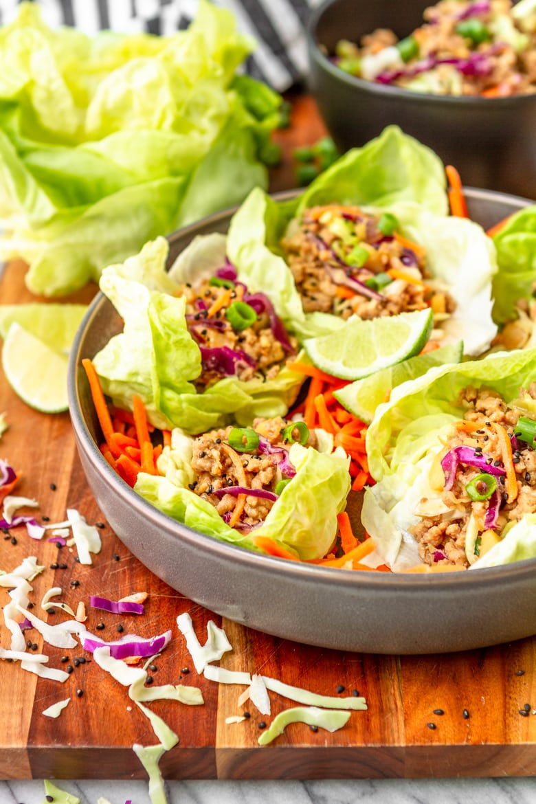pork lettuce cups in a gray bowl on a wooden cutting board