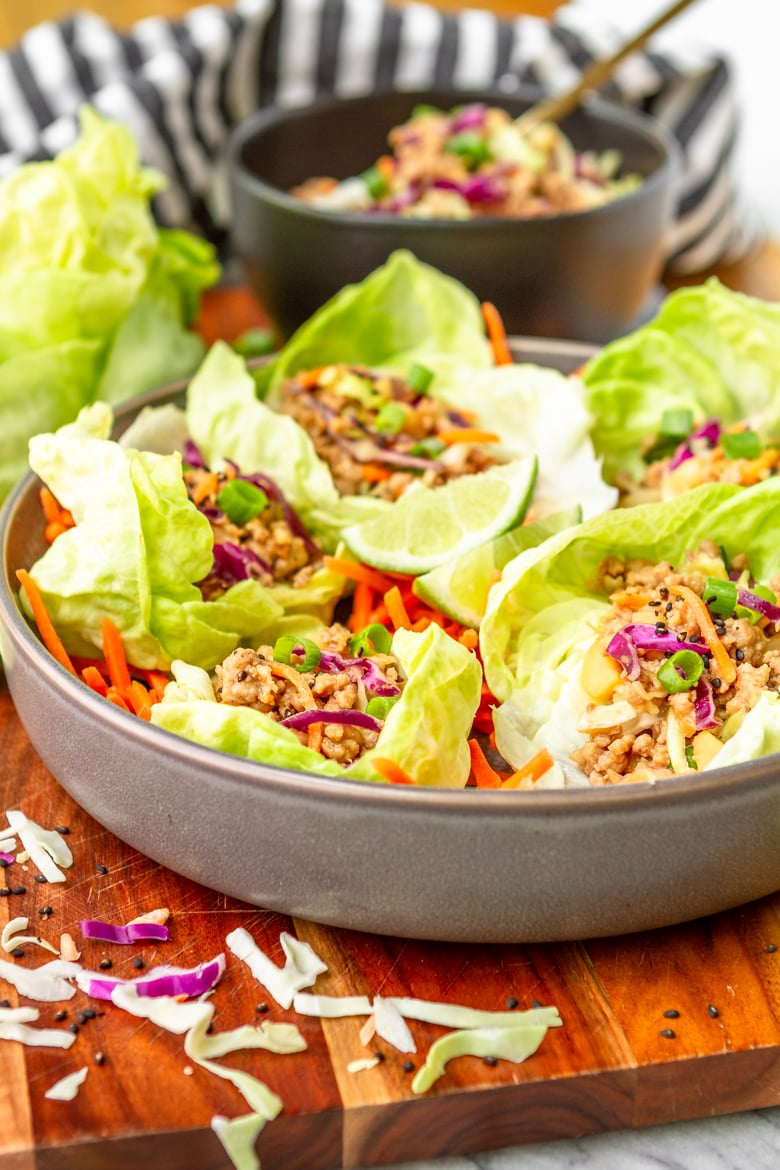 pork lettuce wraps in a gray bowl garnished with green onions and toasted sesame seeds