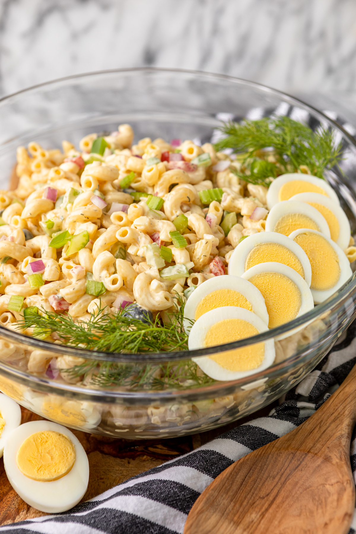 best macaroni salad for a crowd in a large glass bowl garnished with sliced hard-boiled eggs and fresh dill