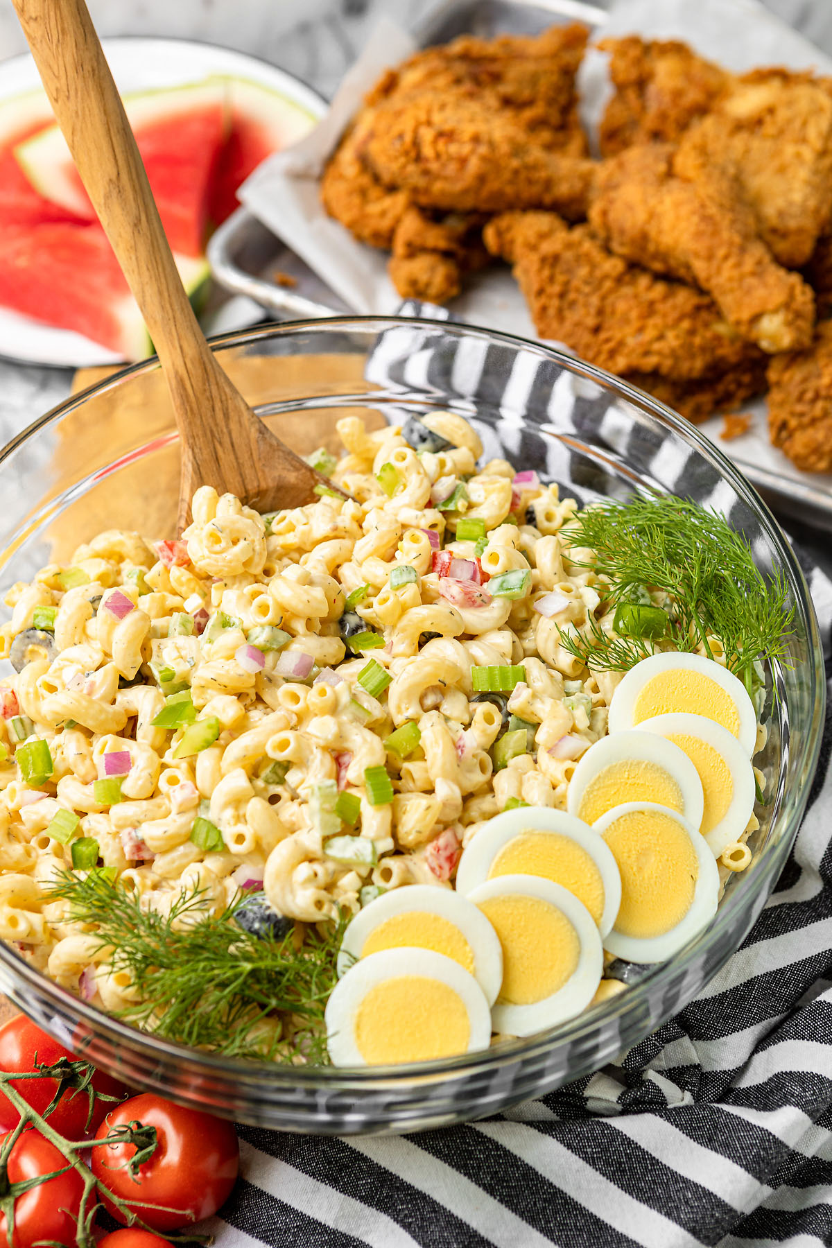 classic macaroni salad with egg in a glass bowl with watermelon slices and fried chicken in the background