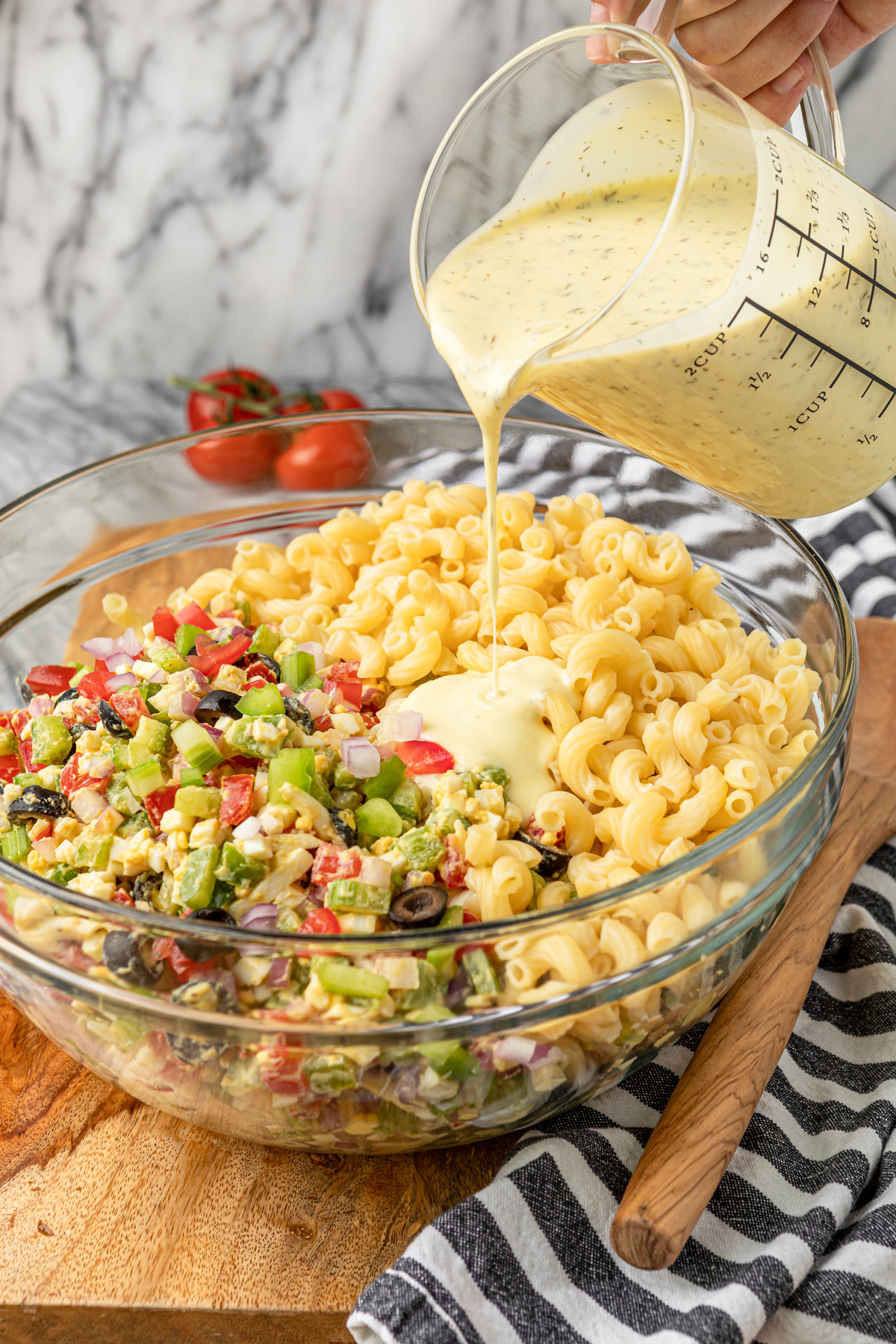 how to make macaroni salad pouring macaroni salad dressing over ingredients in a glass bowl