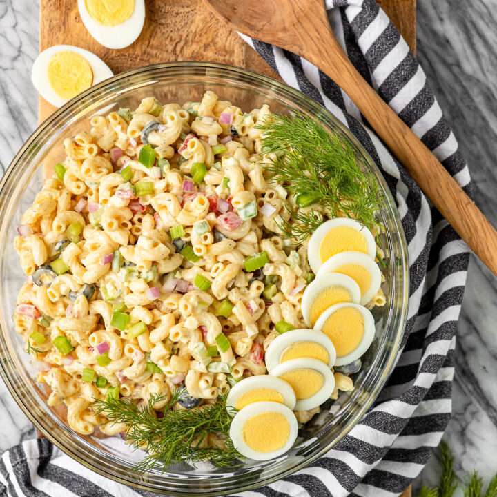 macaroni salad with egg recipe in a glass bowl garnished with hard boiled eggs and fresh dill