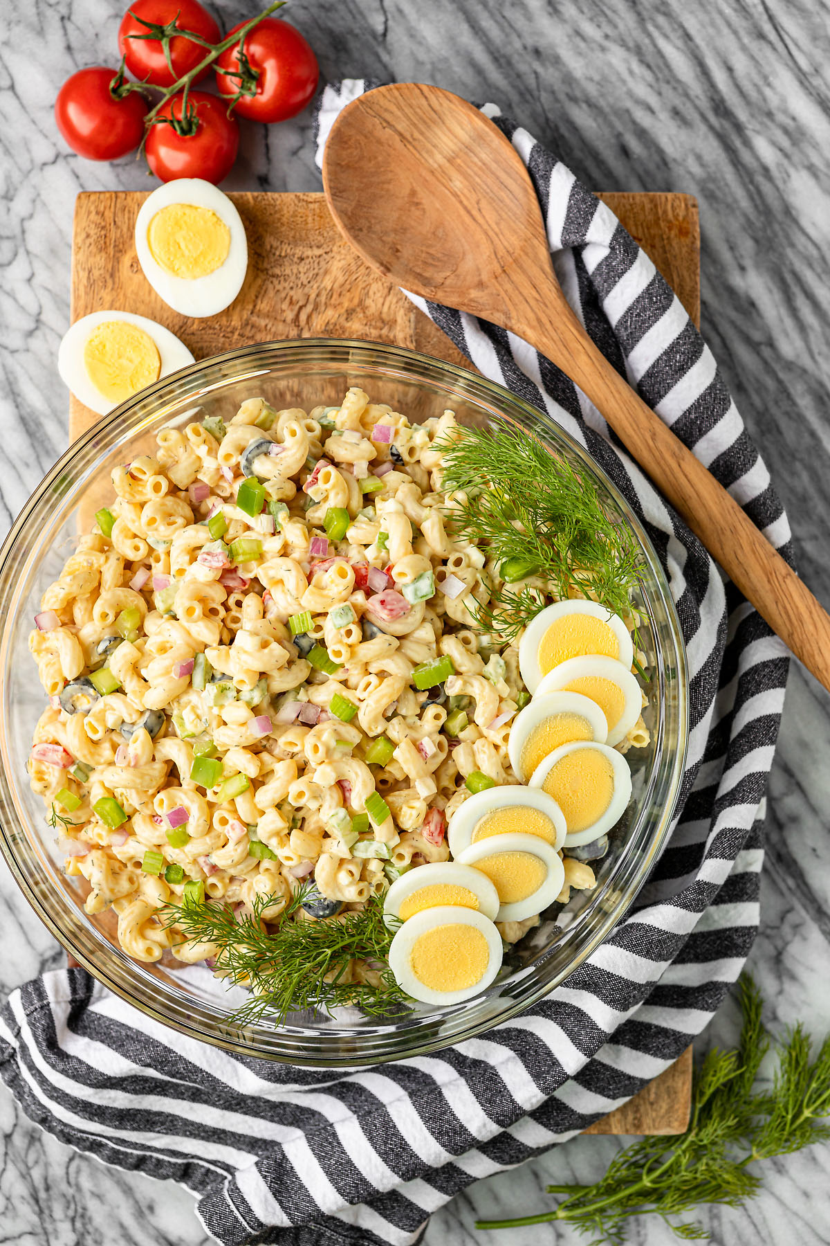 macaroni salad with egg in a glass bowl garnished with hard boiled eggs and fresh dill and a wooden spoon on the side
