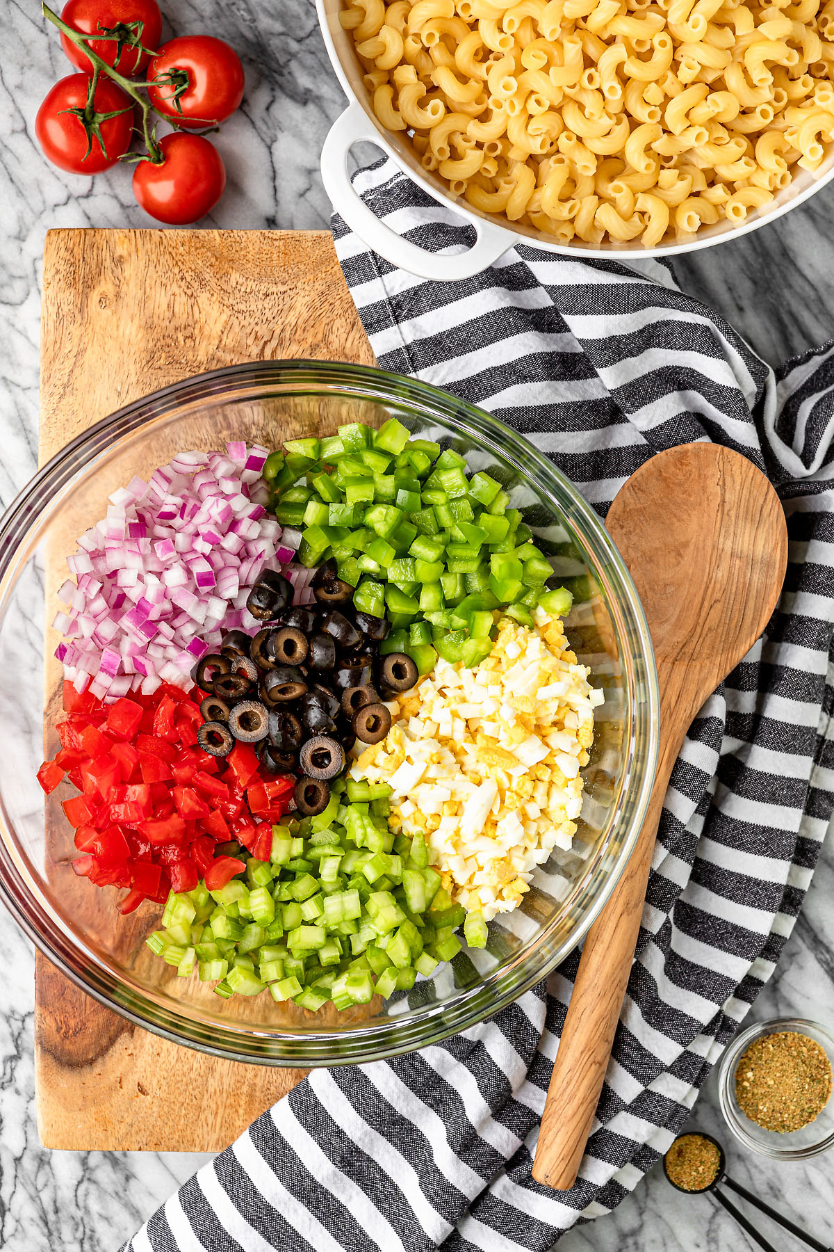 old fashioned macaroni salad ingredients in a glass bowl with a black and white kitchen towel