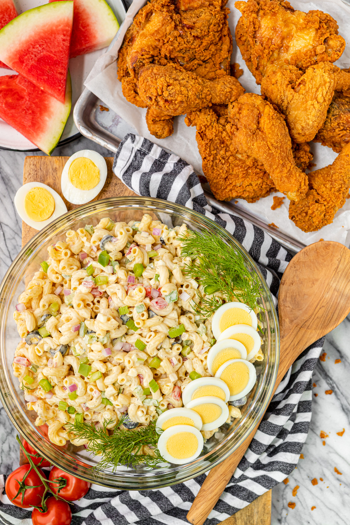 classic macaroni salad in a bowl paired with Walmart deli fried chicken and fresh watermelon slices