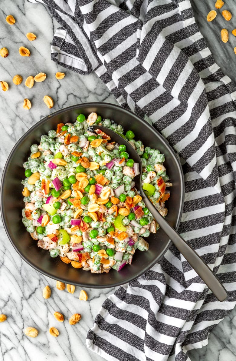 cold pea salad with bacon and peanuts in a black bowl with a black and white kitchen towel
