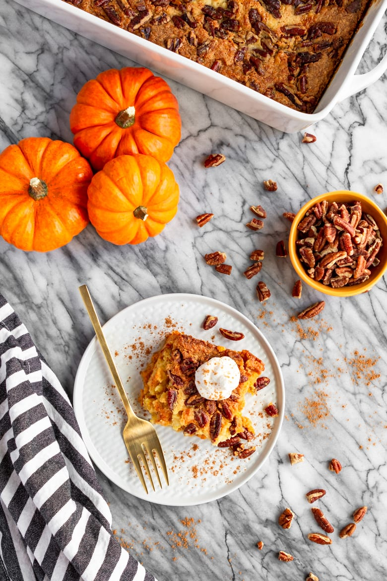 easy pumpkin dump cake recipe served with whipped cream and pecans